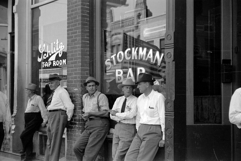 Stockmen in front of the Stockman bar on main street, Miles City, Montana. Other window shows Schlitz Tap Room.