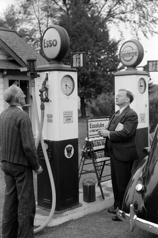 2 men looking at an Esso and Essolene gas pump.