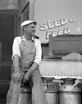 farmer sits on a milk can outside a Seed and Feed store