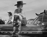 Girl sits on a Chevy Deluxe at a rodeo in Ashland Montana in the 1940's