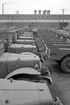 The Chrysler Corporation Dodge truck plant in Detroit Michigan shows Dodge Army trucks lined up side by side and end to end. The trucks are awaiting waiting final touches that make them effective fighting vehicles.