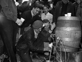 A keg of beer was opened at the scrap salvage campaign in Butte Montana. A young man pours beer from a keg while others wait cup in hand.