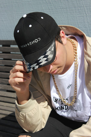 Shop Consttant designer caps and pair with a vintage windbreaker and large gold chain