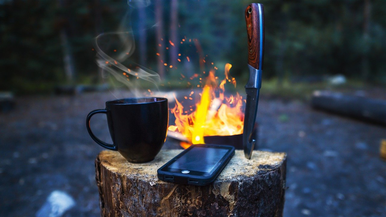 An iphone at a campsite with a fire, a knife, and a mug