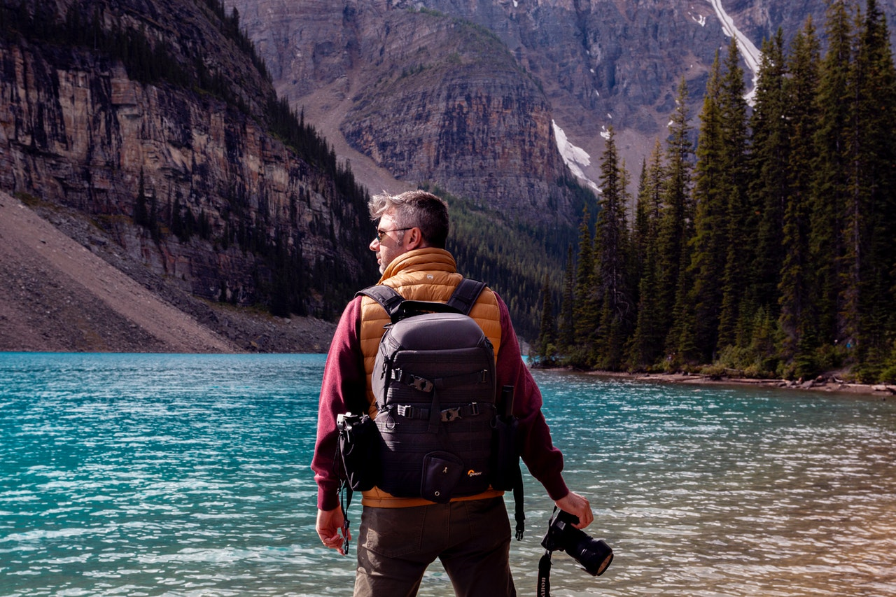 A photographer in the wilderness with a camera and a hiking power bank