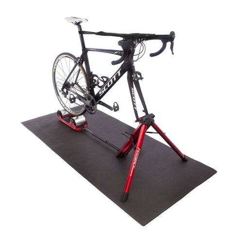 Feedback Sports Omnium Portable Cycle Trainer with Bicycle on Floor Mat