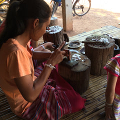 Woman at work making silver beads