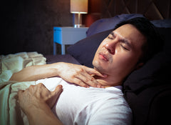 Man in bed with heartburn