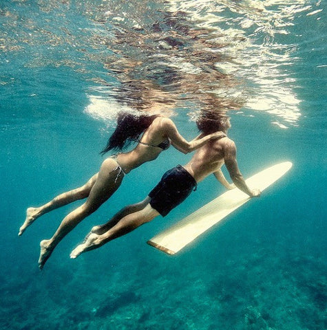 man & woman swimming with surf board