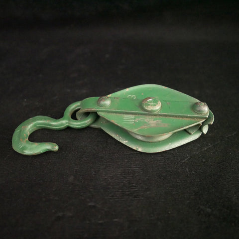 Antique green 7-inch single sheave metal block pulley.