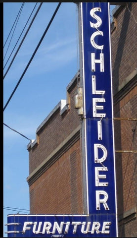 Look for the blue and white Schleider furniture neon sign located at 307 S Austin St in downtown Brenham