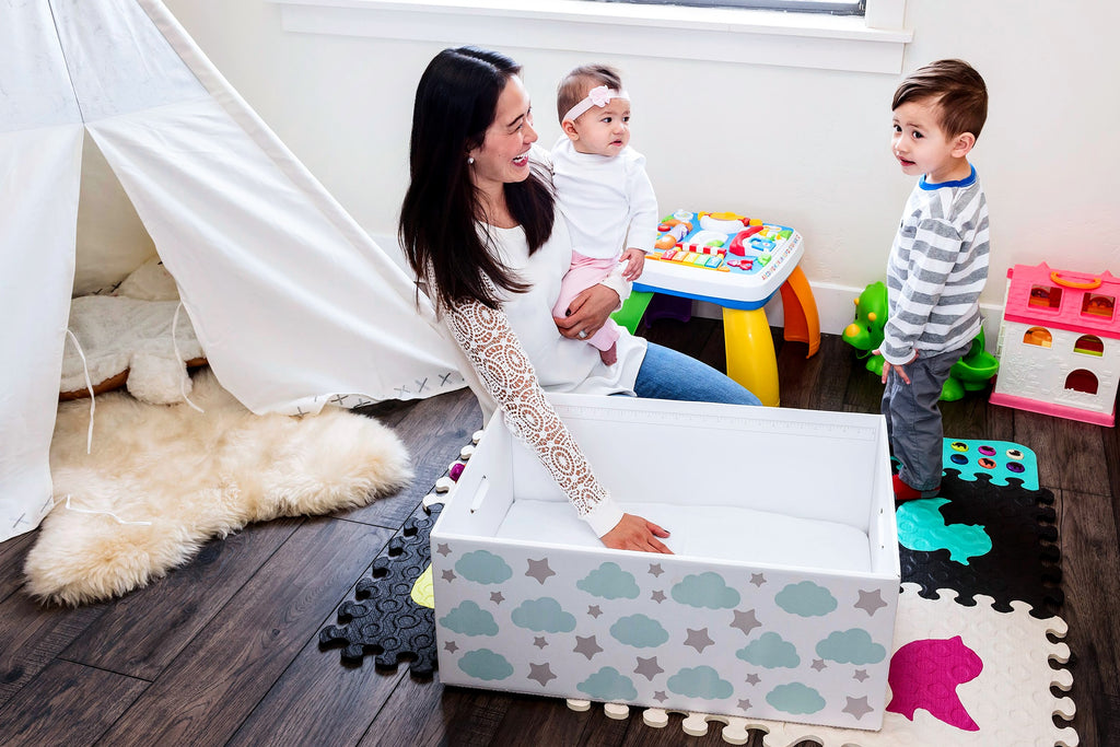 Mom playing with boy toddler and young daughter in nursery with a baby box bassinet