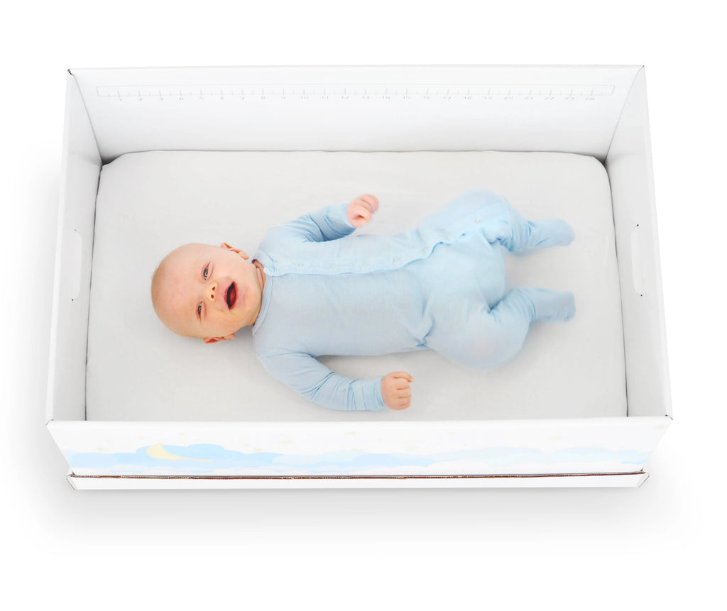 Cute baby boy wearing a blue Kickee Pants onesie sleeping in a baby box bassinet