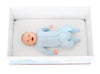 Smiling Baby in a blue onesie laying in a Finnish baby box
