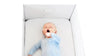 Sleeping baby in blue onesie yawning inside a Finnbin baby box