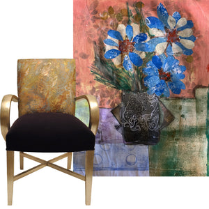 Eclectic lounge chair with black seat and gold pattern back. Frame has rounded golden armrest and legs. Large artwork behind the chair with blue and white flowers in a dark pot and pink, green and purple background.