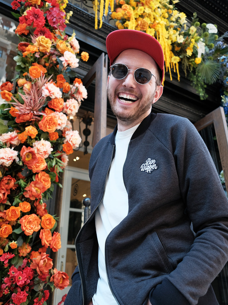 The Dapper Bomber Jacket in front of a rainbow flower storefront