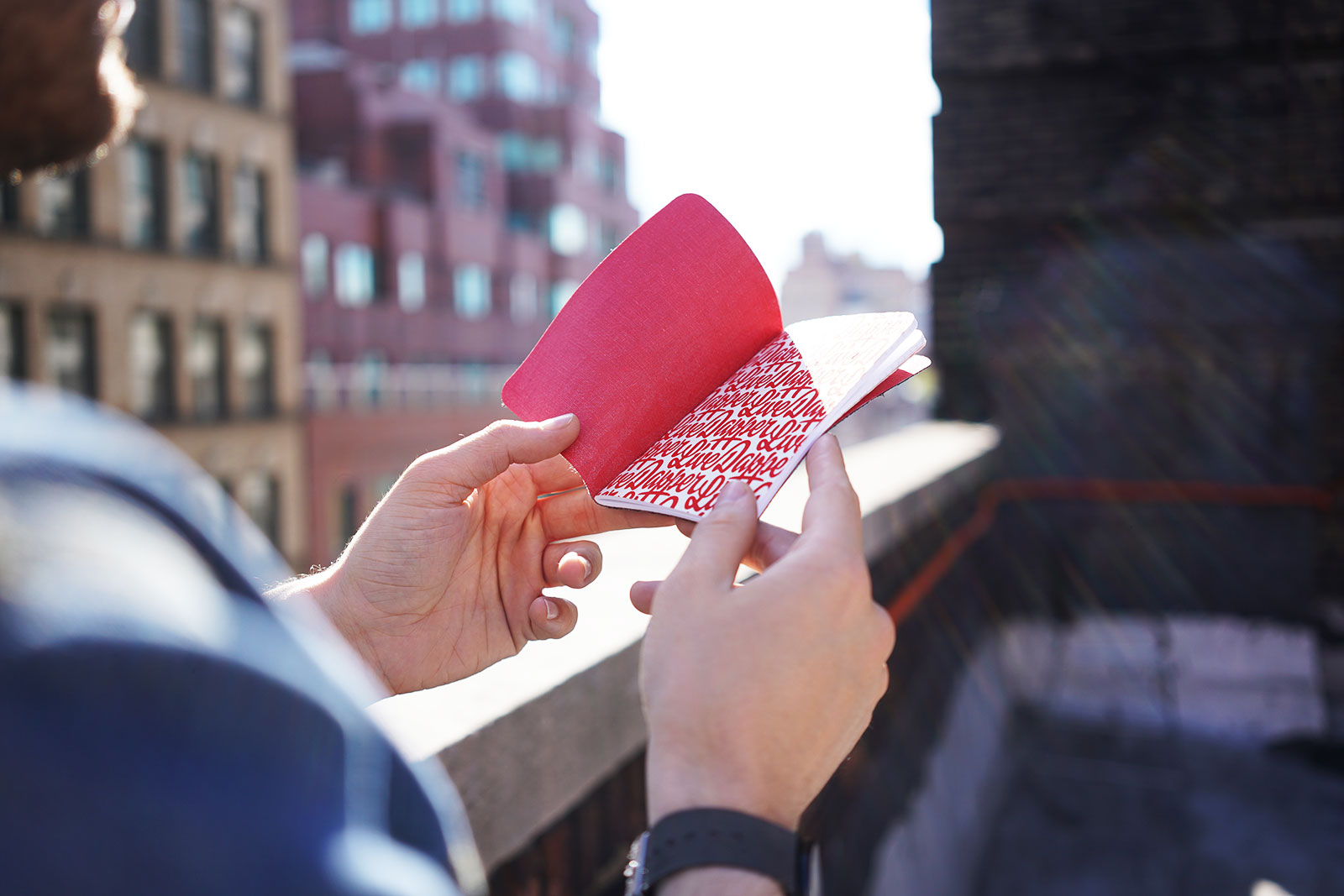 Pocket notebook in New York City with sun rays and building in the background