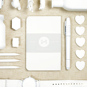 white pocket notebook with white object knolling