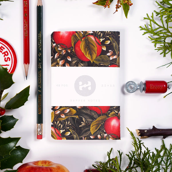Pocket notebook with an apple and foliage themed cover, presented on a tabletop alongside other items like musgrave pencils, a bird call, and chirstmas-ey plants