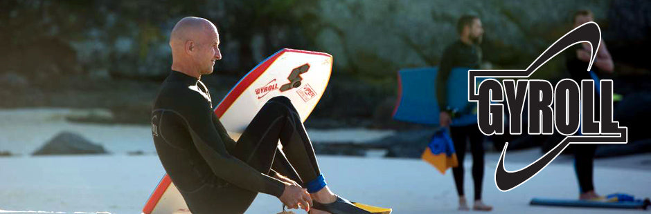 Man in black wetsuit and swimfins sitting with bodyboard leaning on his knee with Gyroll logo