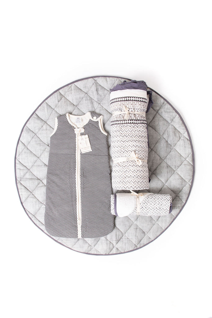 This beautiful neutral gift-set by Malabar baby is the perfect baby shower or newborn gift. This gift set comes with a handmade grey, brush-stroked play and nap mat, a handmade, GOTS certified organic cotton wearable blanket baby sleeping bag sack, a handmade block-printed hooded towel that fits newborns-toddlers 4 years old, and a handmade block-printed natural cotton crib quilt. The best part is that everything in this gift-set matches. This set is highly recommended and is a go-to baby gift.