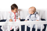 Two babies playing in a crib, laughing and having fun in Malabar baby's handmade and organic sleep sacks. Southside blue fitted crib sheet is shown on the crib and the babies are dressed in the following colors; for blue and white and miami pink and teal.