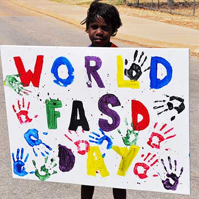 Young boy holding World FASD Day sign