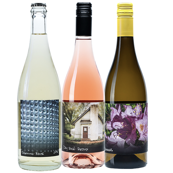 750ml bottles of Sparkling White, Dry Rosé Reudx and Vignoles are lined up next to each other.