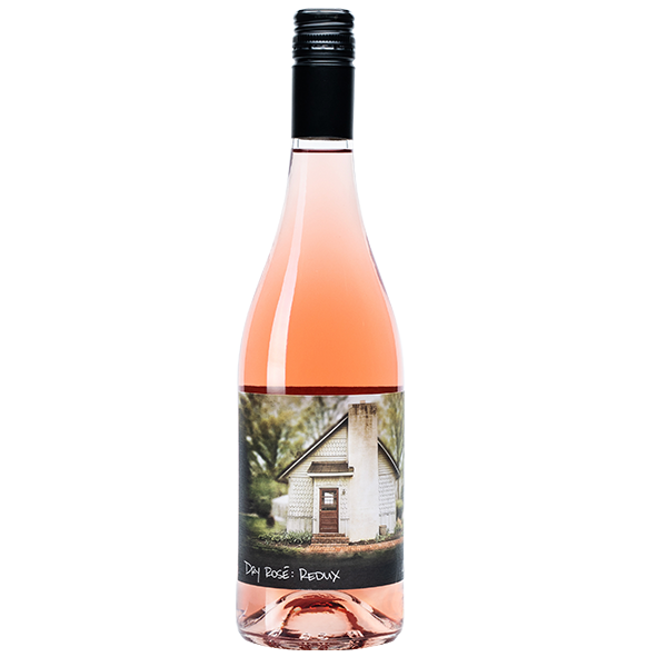 750ml bottle of Dry Rosé Redux. Clear bottle with black screw top. Label shows the cottage on property.