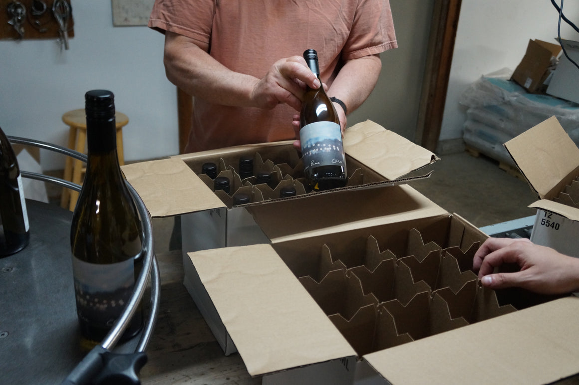 Employees placing bottles of Sauvignon Blanc into boxes on the bottling line
