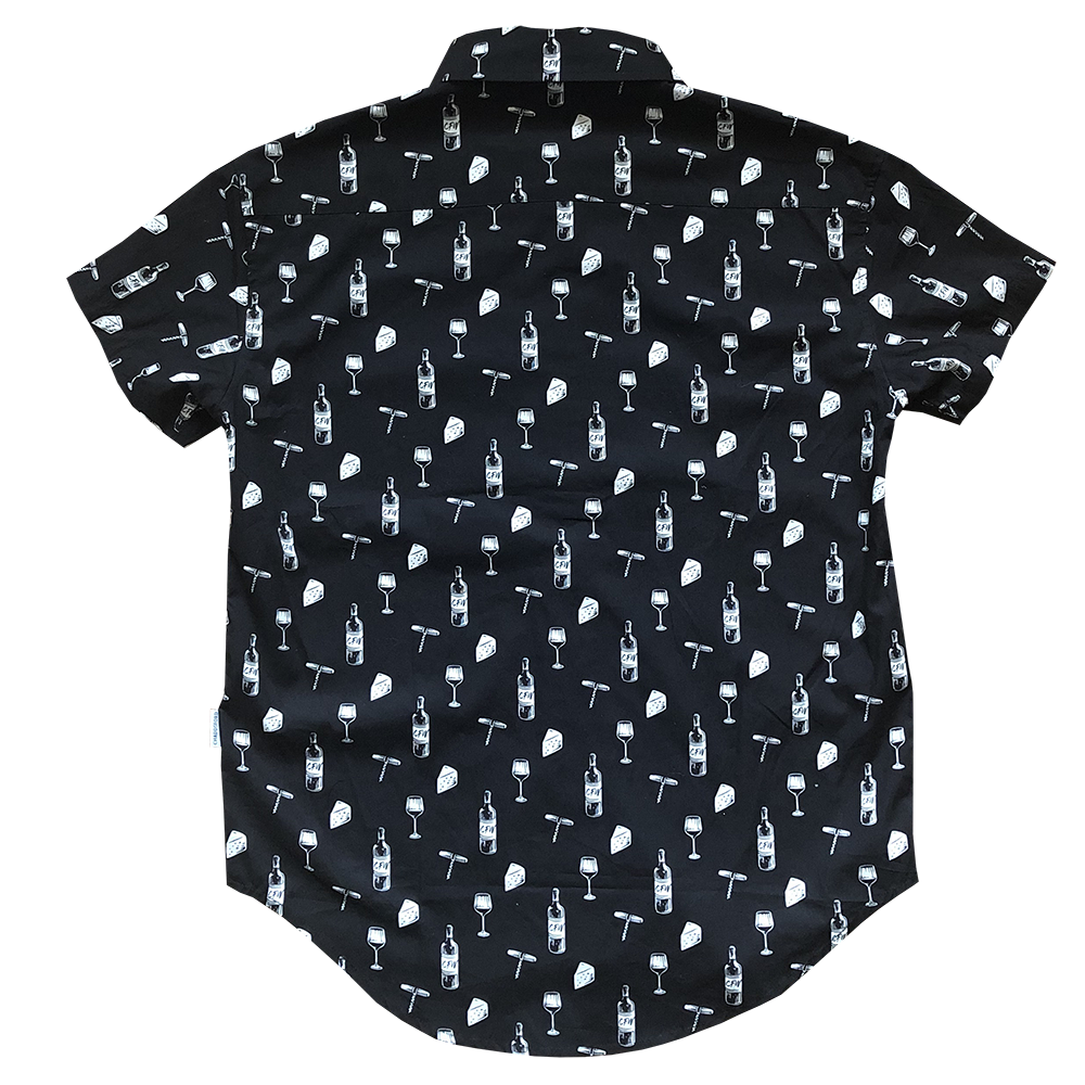 Back of women's black button up shirt. Design pattern features repeated glasses of wine, cheese blocks, bottles of wine and wine openers in white.