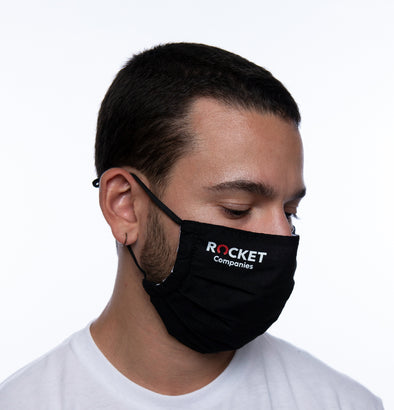 Head and shoulders of a person wearing a black mask with Rocket Companies logo imprint.