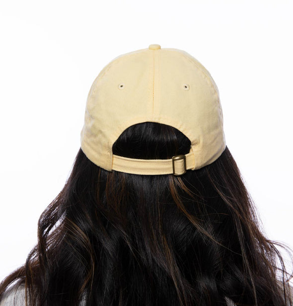 Back image of a person wearing a butter yellow hat with DET embroidered on the front.