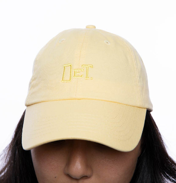 Person wearing a butter yellow hat with DET embroidered on the front.
