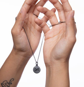 Hands holding a black necklace and charm with DET imprint.