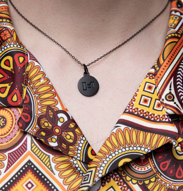 Close up image of a person wearing a black necklace and charm with DET imprint.