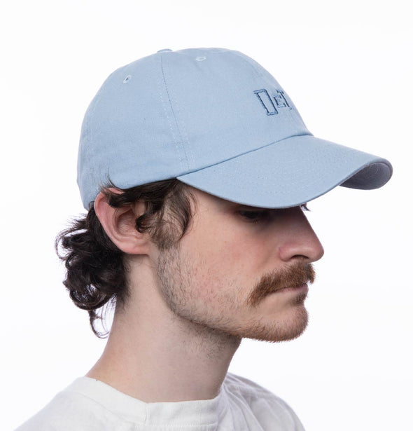 Person wearing a sky blue hat with DET embroidered on the front.