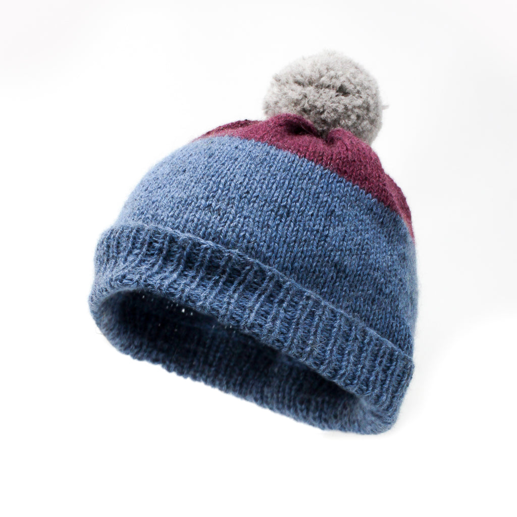 A hand knitted product using Forget-Me-Not blue and Mountain Berry red topped with a Natural Grey pom pom
