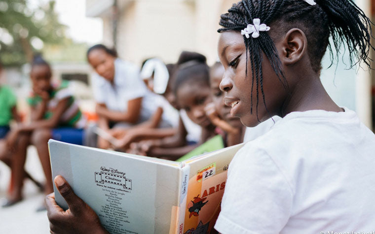 Girl reading book to class