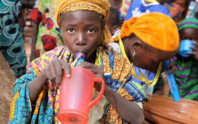 child drinking water from a Water is Life Straw