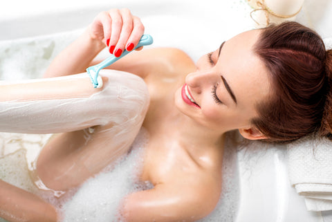 young woman shaving her legs in the bathtub with a blue razor