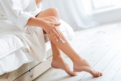woman applying body butter to legs