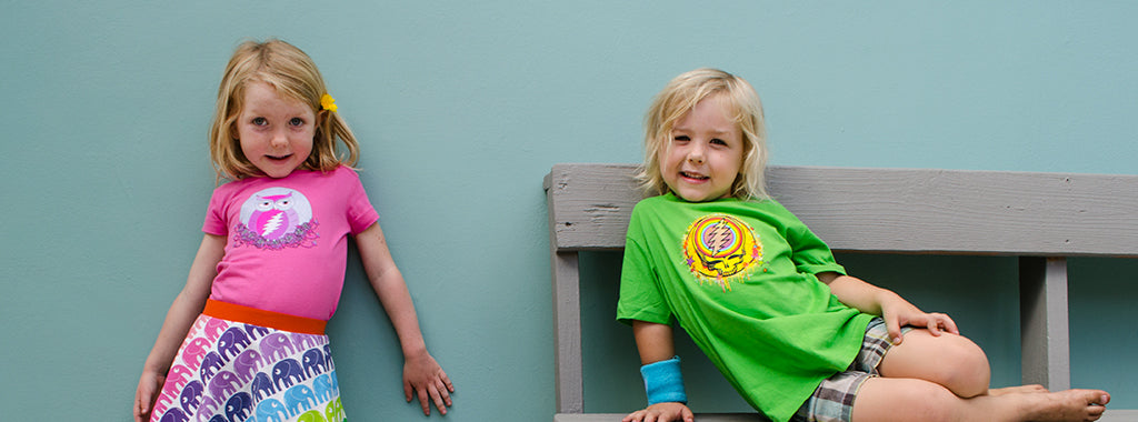 Hippie kids on a wooden bench wearing Grateful Dead tees by Little Hippie