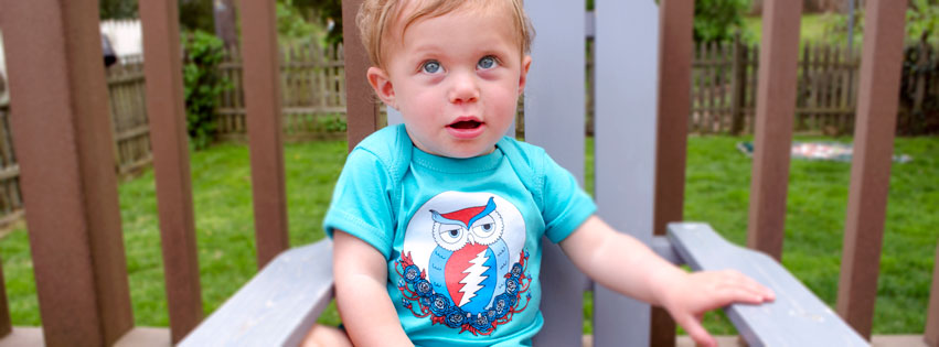 a3580b57373 Adorable Hippie baby wearing a Grateful Dead Owl onesie sitting on a wooden  bench outdoors