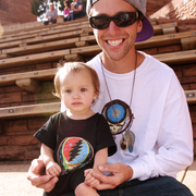 Dad wearing a Grateful Dead Steal Your Face skull in a dream catcher with white and blue feathers hanging from it, on a white unisex adult long sleeve tshirt, sitting on stone and wood stadium bleachers, with his baby girl wearing a black Little Hippie Calaveras baby romper