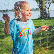 A blonde toddler grinning and playing in a sprinkler, wearing the blue Rainbow Bears toddler tee.