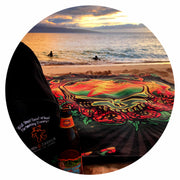 The Scarlet Fire fleece blanket spread out on a beach by the ocean, with a Wall Street Dead Ahead backpack and a beer bottle sitting on the left bottom corner, and surfers in the ocean.