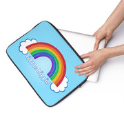 Hands putting a laptop into the Little Hippie Rainbow laptop sleeve.