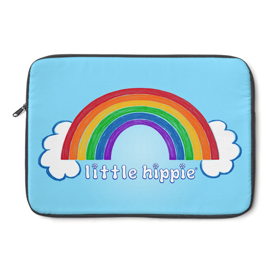 A light blue laptop sleeve that has a rainbow with clouds at both ends, with the Little Hippie logo under it.